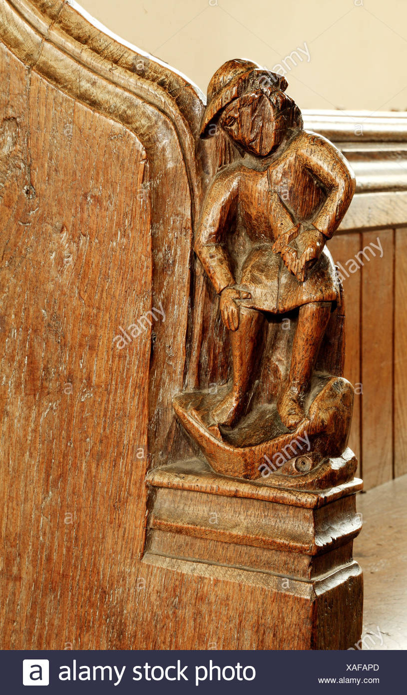 Medieval bench end, Anger, Seven Deadly Sins, angry man with knife in Jaws of Hell, carved wood art English bench ends Thornham - Stock Image