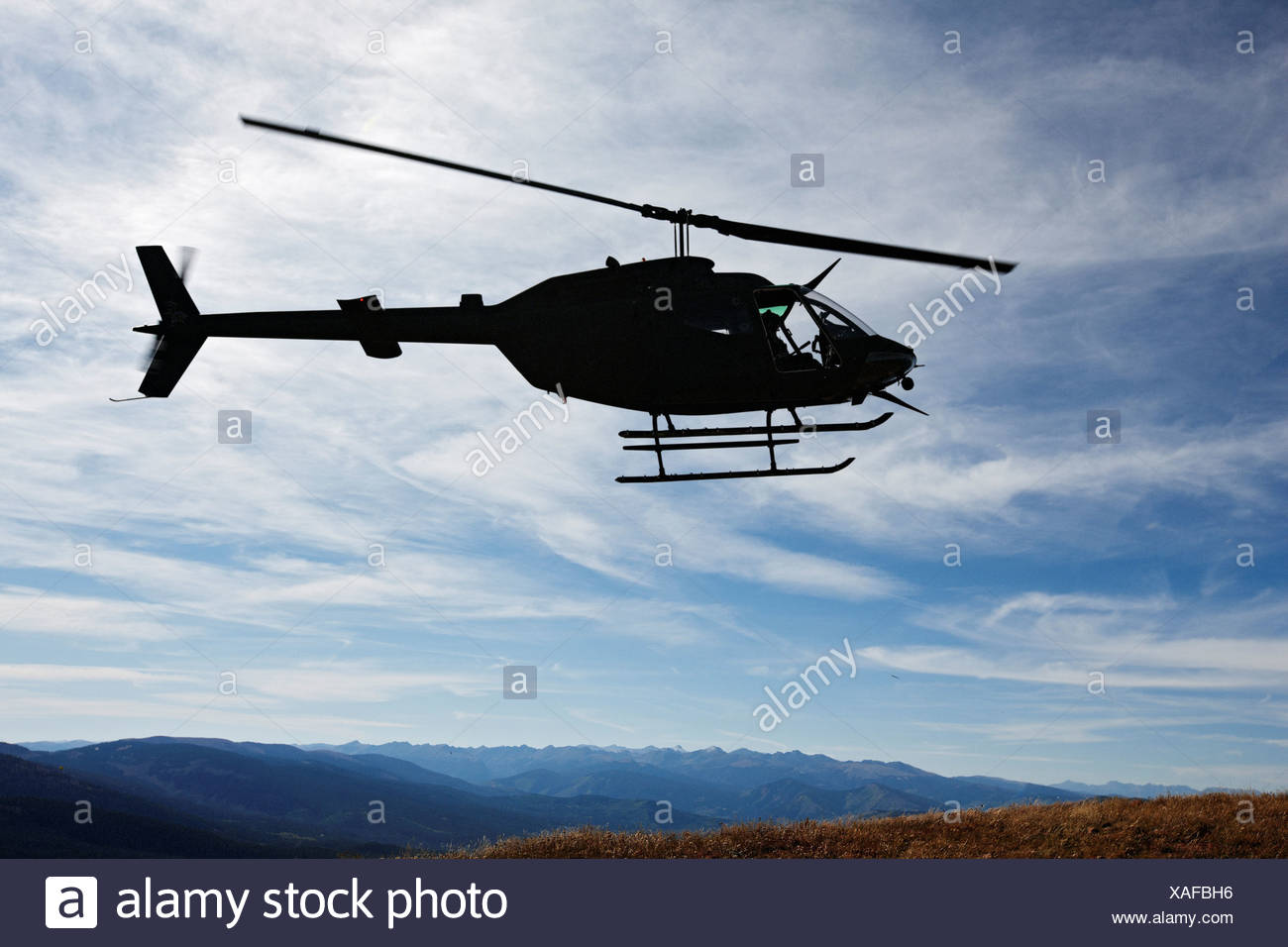 Silhouette of a U.S. Army National Guard OH-58 Kiowa in Colorado's Rocky Mountains. - Stock Image