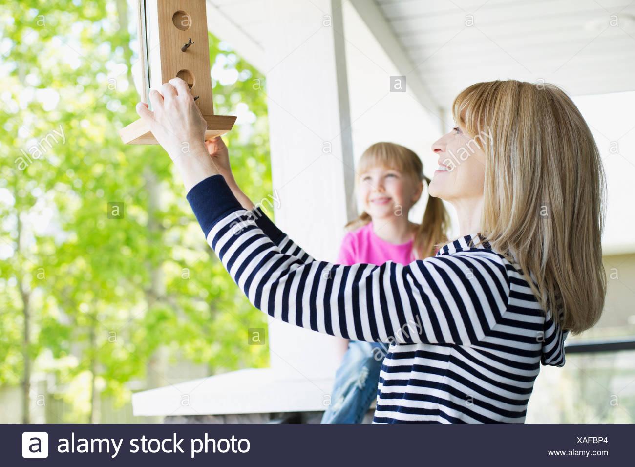 mature woman hanging bird feeder - Stock Image