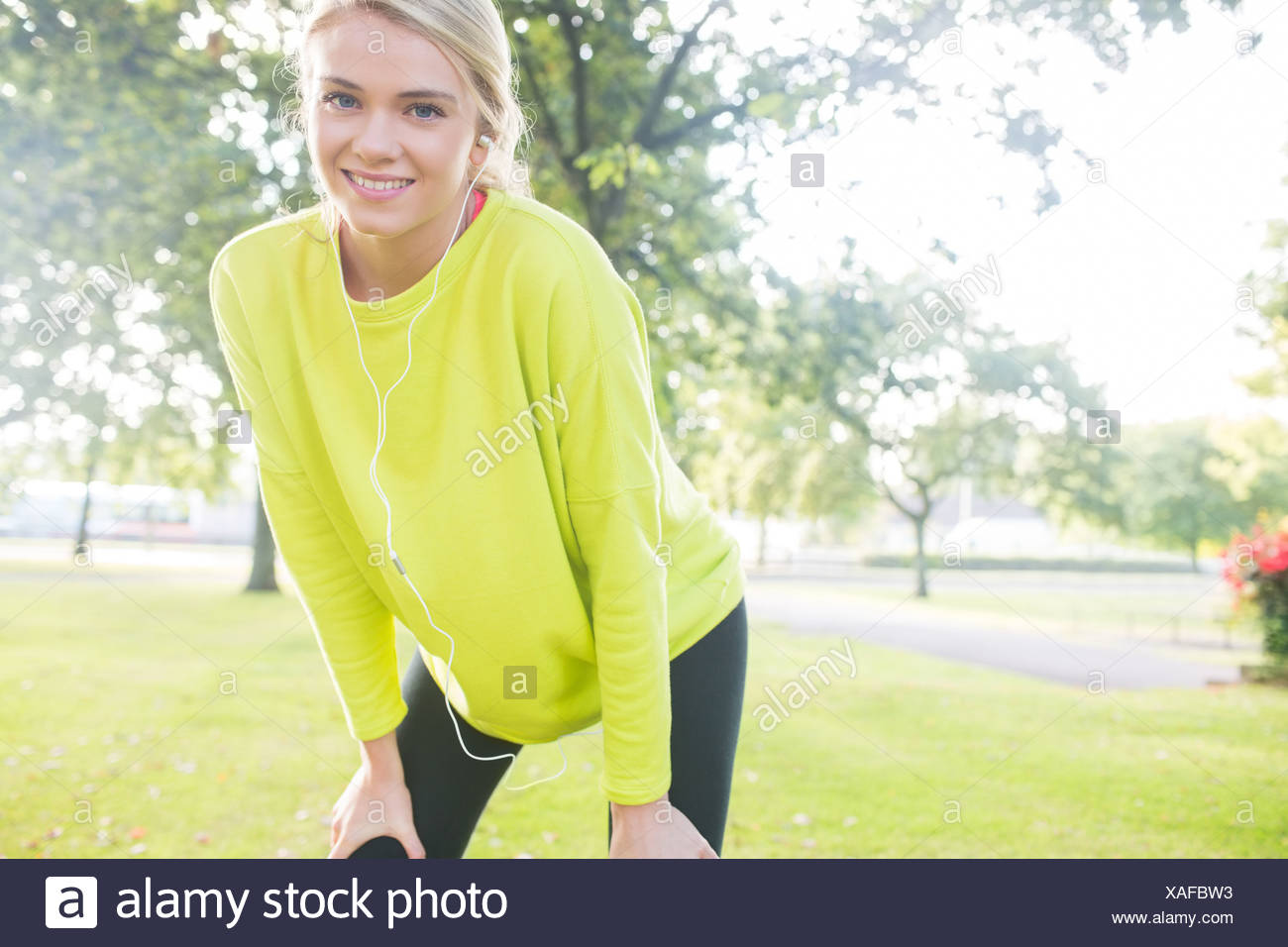 Active cheerful blonde pausing after a run - Stock Image