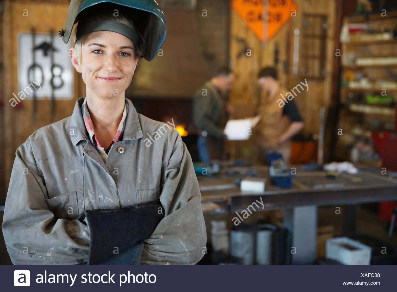 Confident female welder in protective work wear - Stock Image