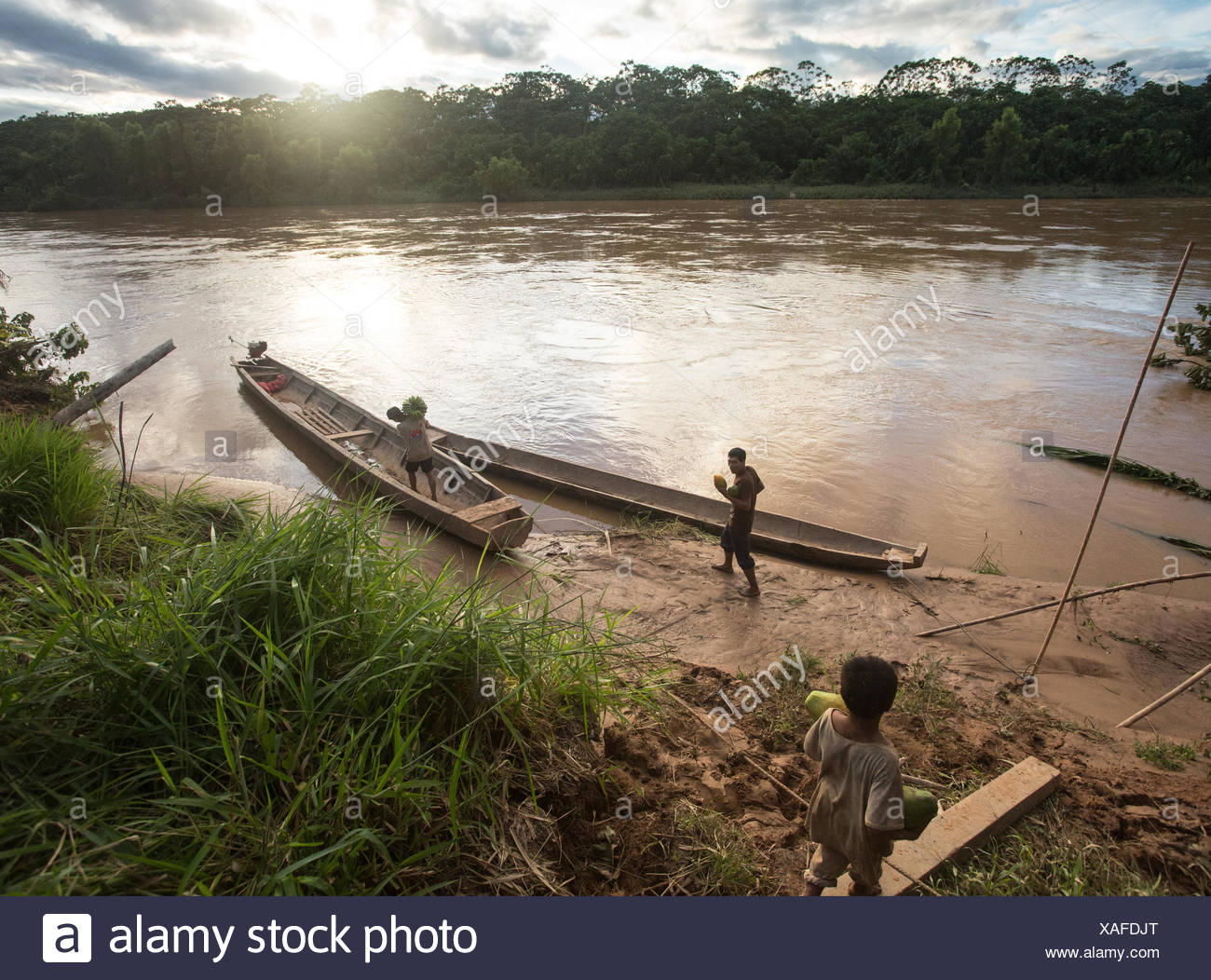 Tsimane people approach a canoe to transport goods on the Maniqui River, near Anachere, in the Amazon rainforest, Bolivia. - Stock Image