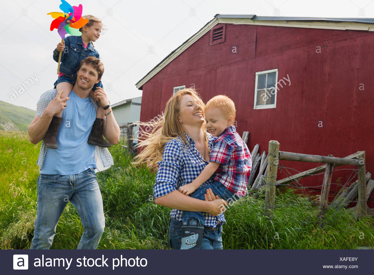 Parents carrying children outside barn - Stock Image