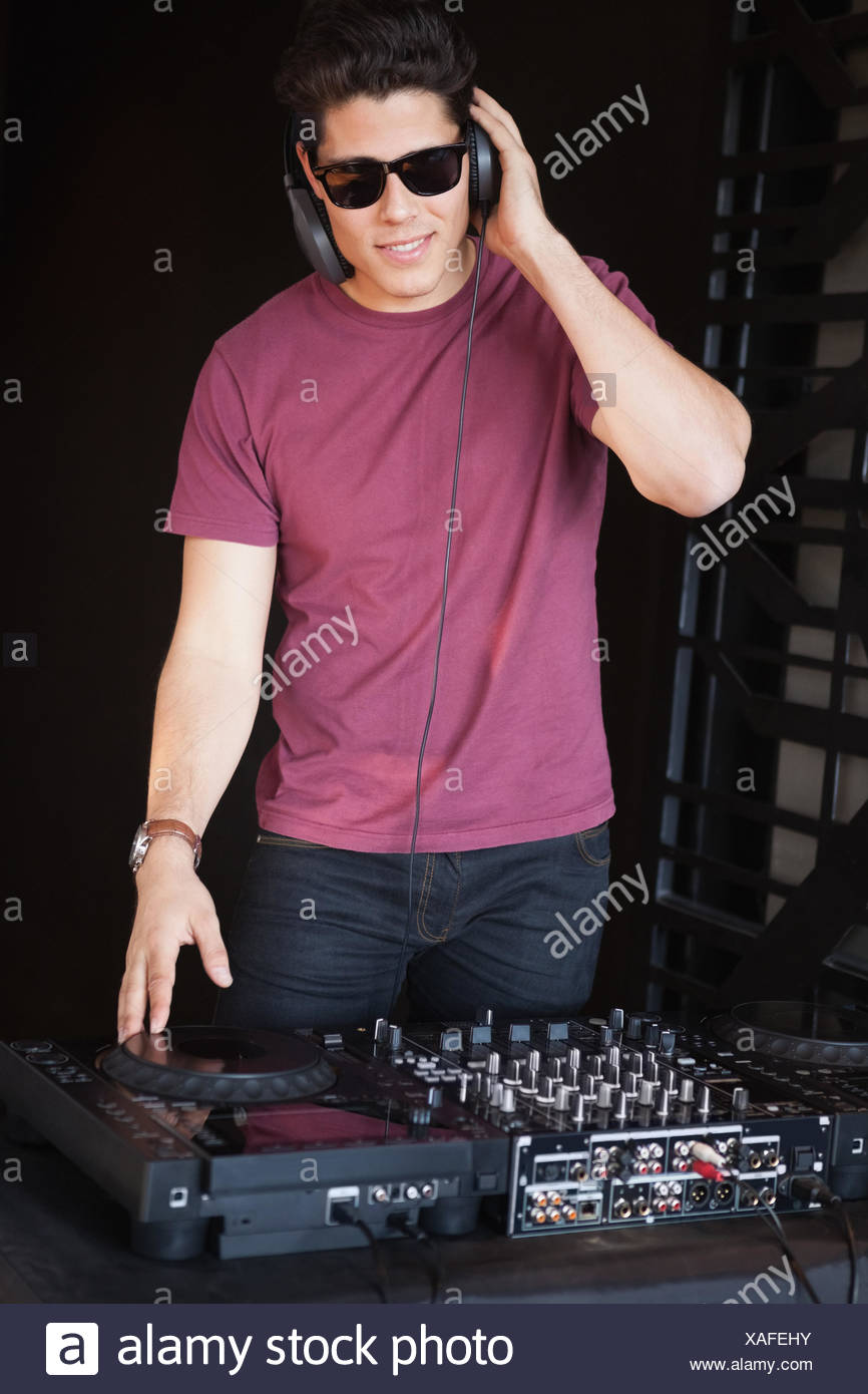 Cool dj in sunglasses spinning the decks - Stock Image