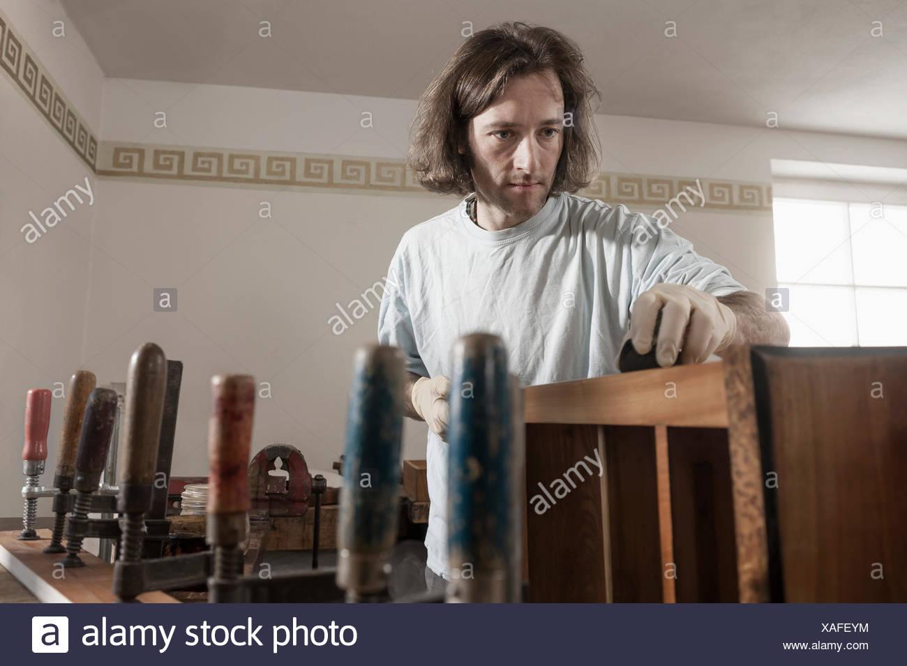 Carpenter French polishing wooden drawer at workshop, Bavaria, Germany Stock Photo