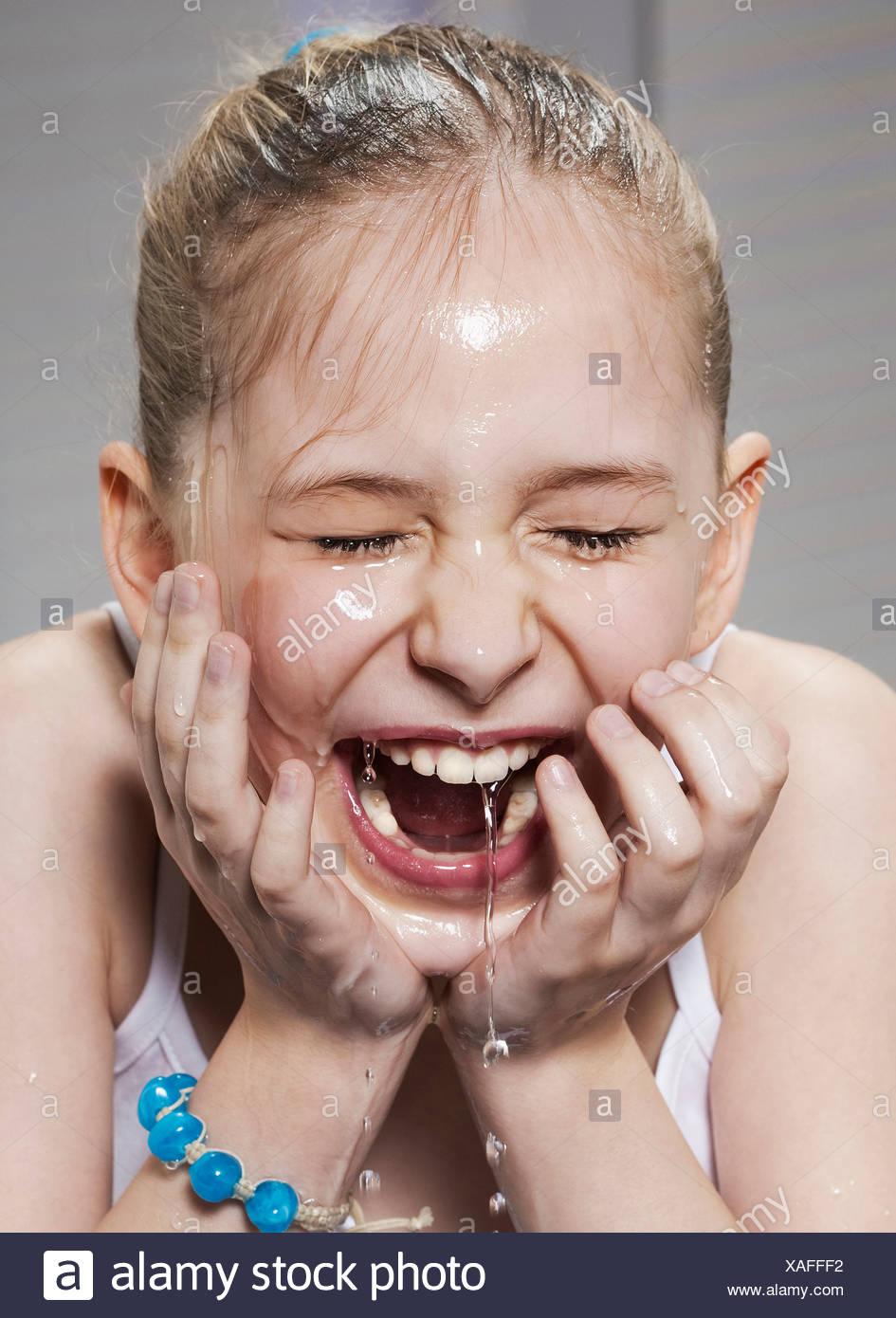 Laughing girl washing her face - Stock Image