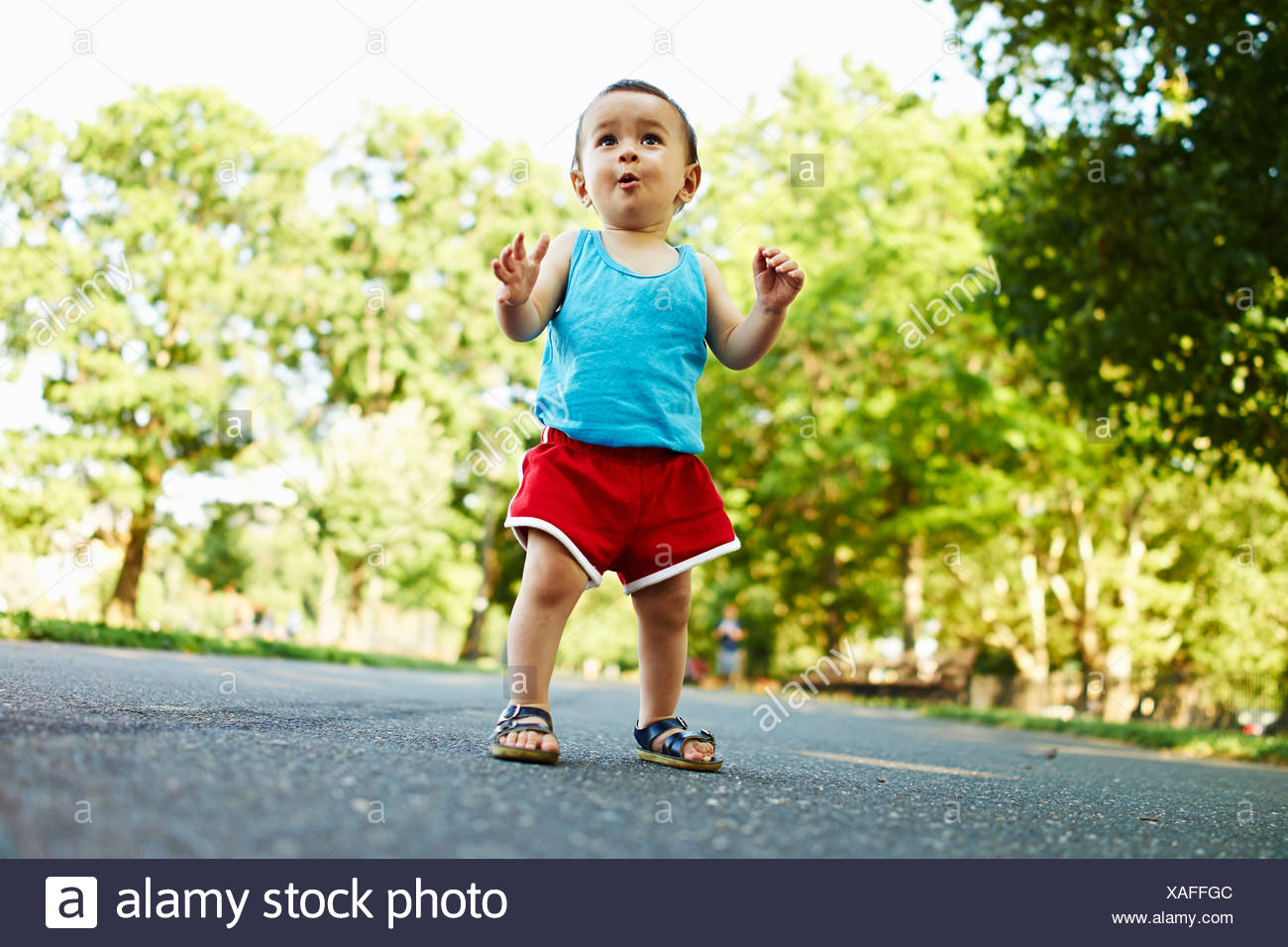 Baby boy standing on park path - Stock Image