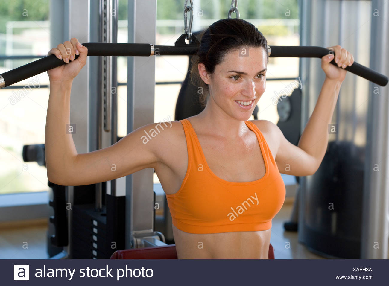 Woman using exercise equipment in gym, smiling, close-up Stock Photo