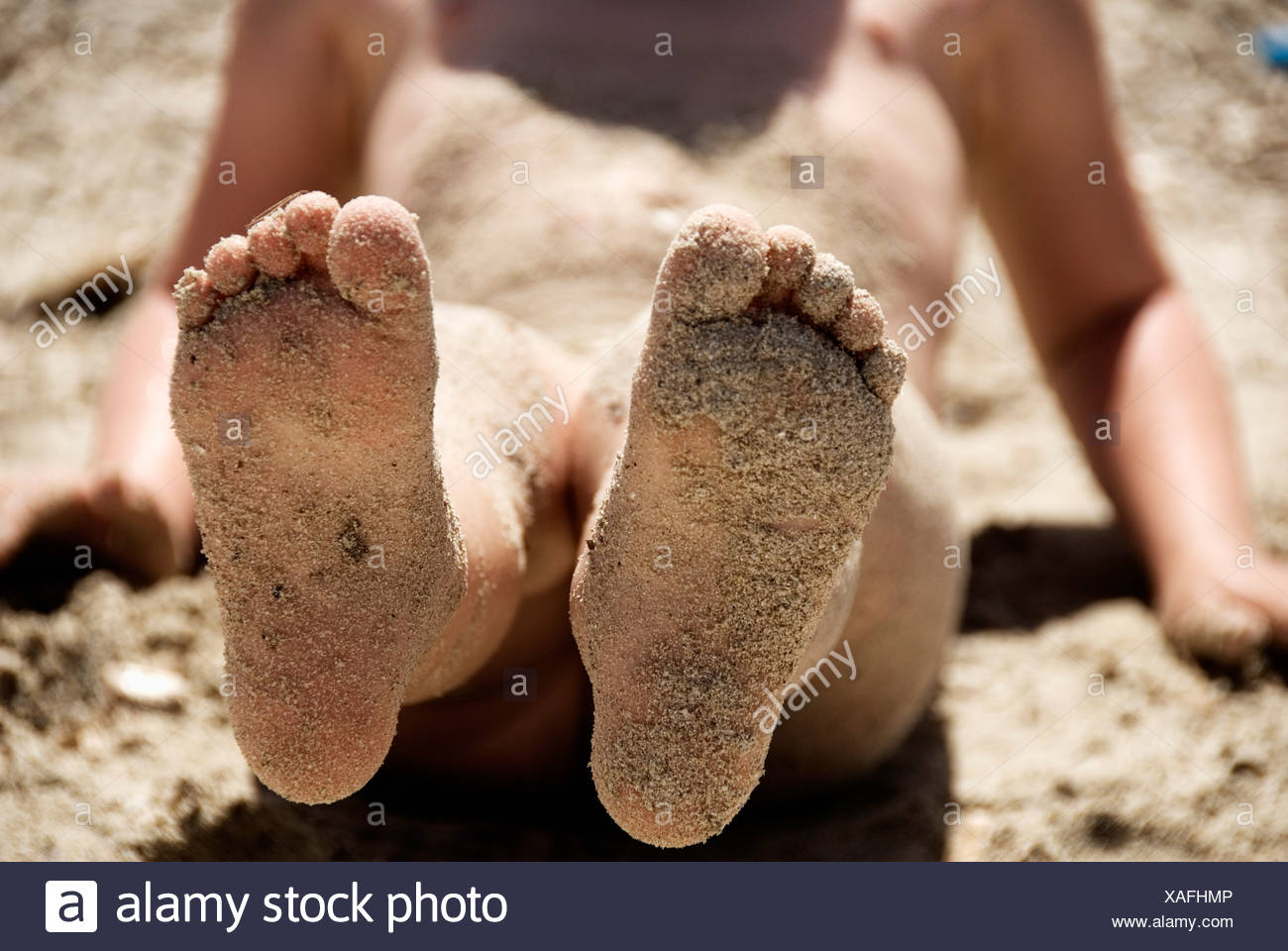 Child with sand on feet - Stock Image