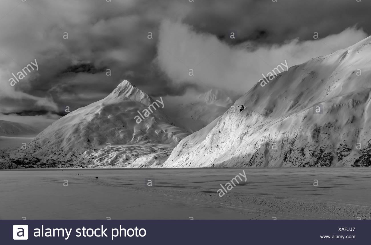 Hikers make the trek to Portage Glacier on Portage Lake in winter, South-central Alaska; Alaska, United States of America - Stock Image