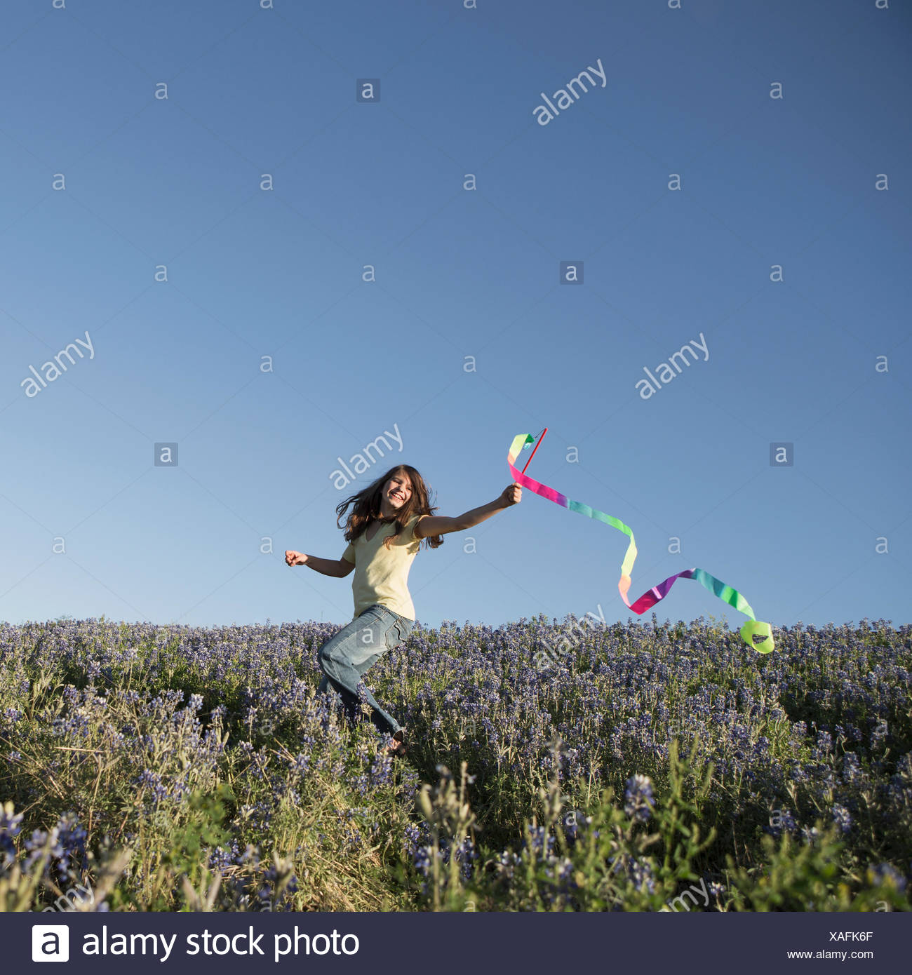 A child, a girl running with a paper streamer fluttering in the wind. - Stock Image