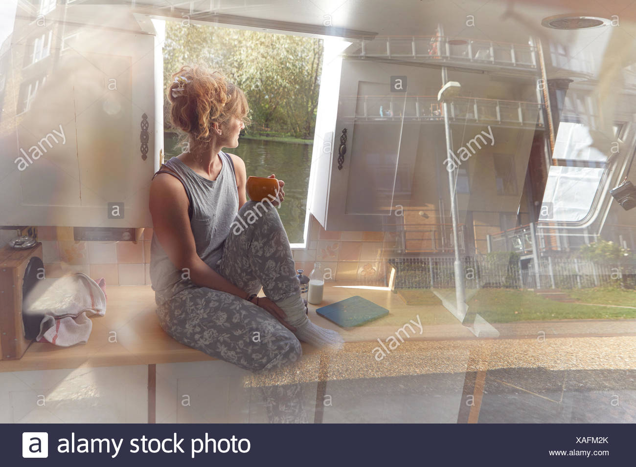 Woman having coffee on canal boat, view through window - Stock Image