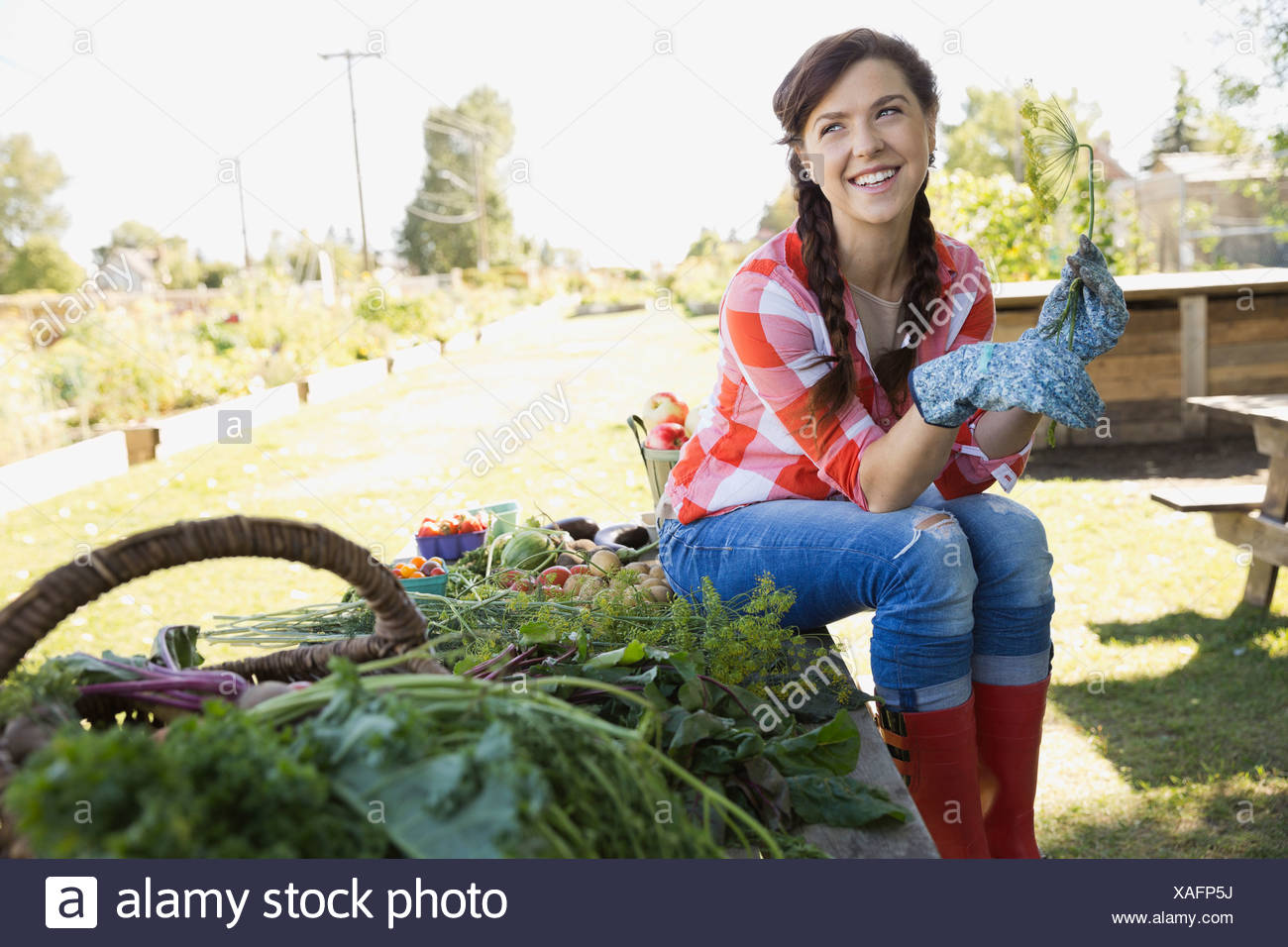 Happy woman sitting in community garden - Stock Image