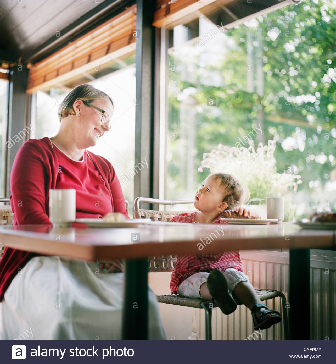Finland, Helsinki, Uusimaa, Grandmother and granddaughter (2-3) relaxing in cafe - Stock Image