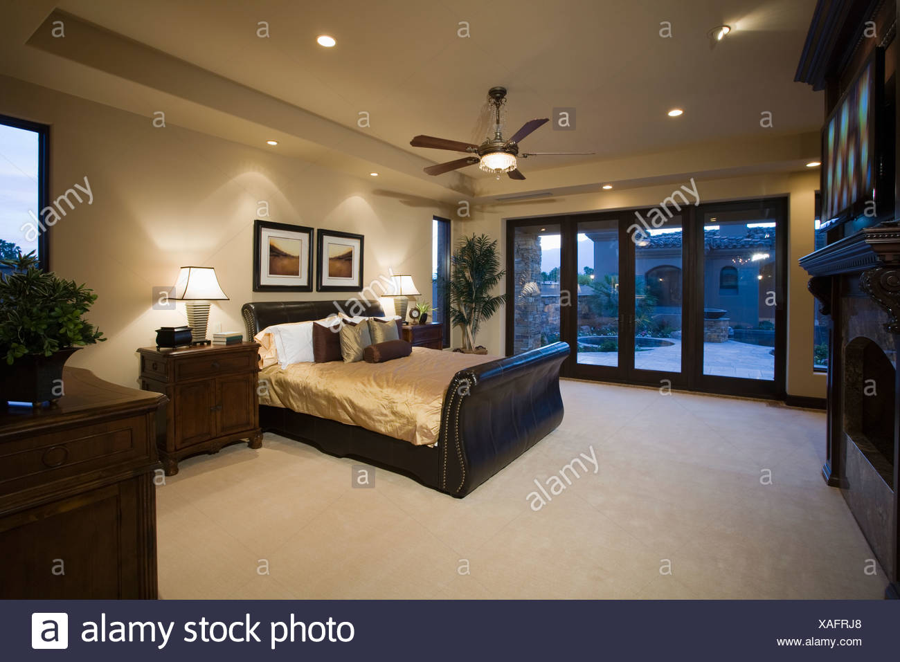 Dark Wood Furniture In Bedroom With Ceiling Fan Stock Photo
