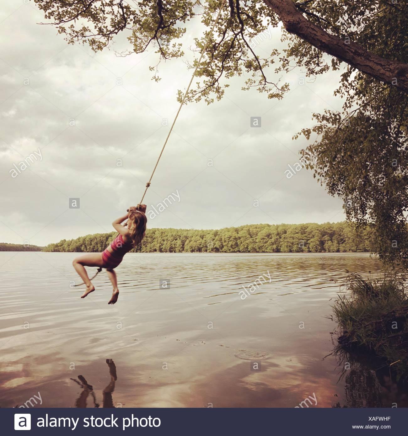 Girl Swinging Over Lake Against Sky - Stock Image