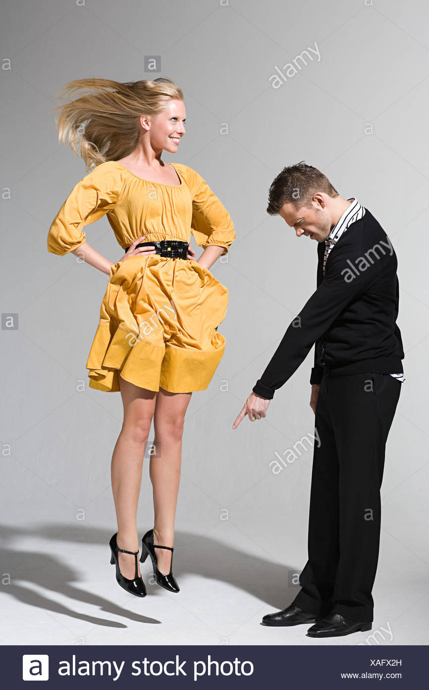 A man pointing at a woman jumping - Stock Image