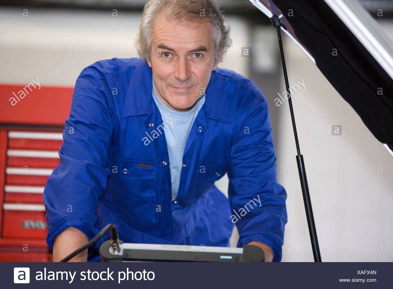 Mechanic with diagnostic computer by car with open bonnet, portrait - Stock Image