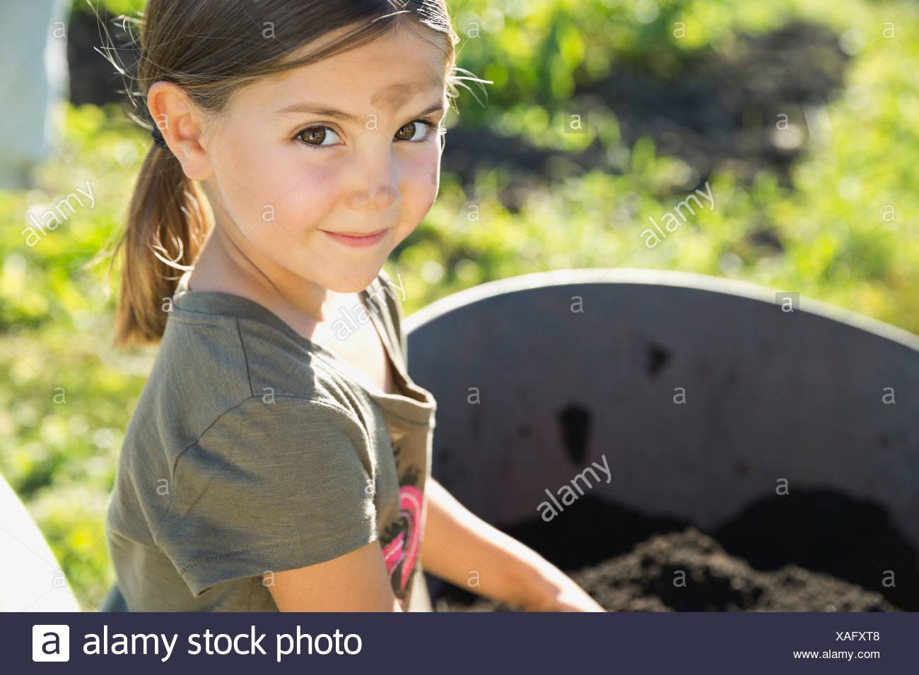 Portrait of cute girl standing next to wheelbarrow Stock Photo