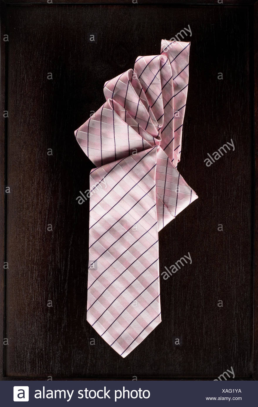 Pink necktie with chequered pattern on brown surface - Stock Image