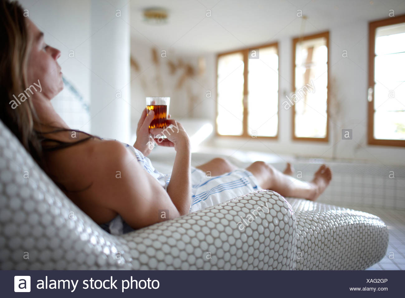 Woman enjoying a cup of tea in a spa hotel, Am Hochpillberg, Schwaz, Tyrol, Austria - Stock Image