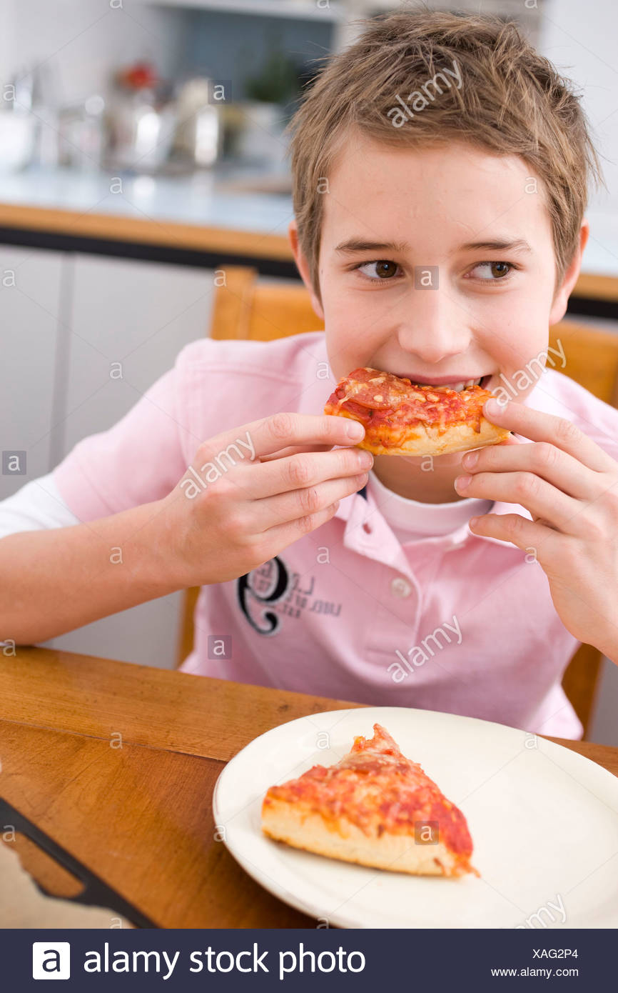 Boy eating a piece of pizza - Stock Image