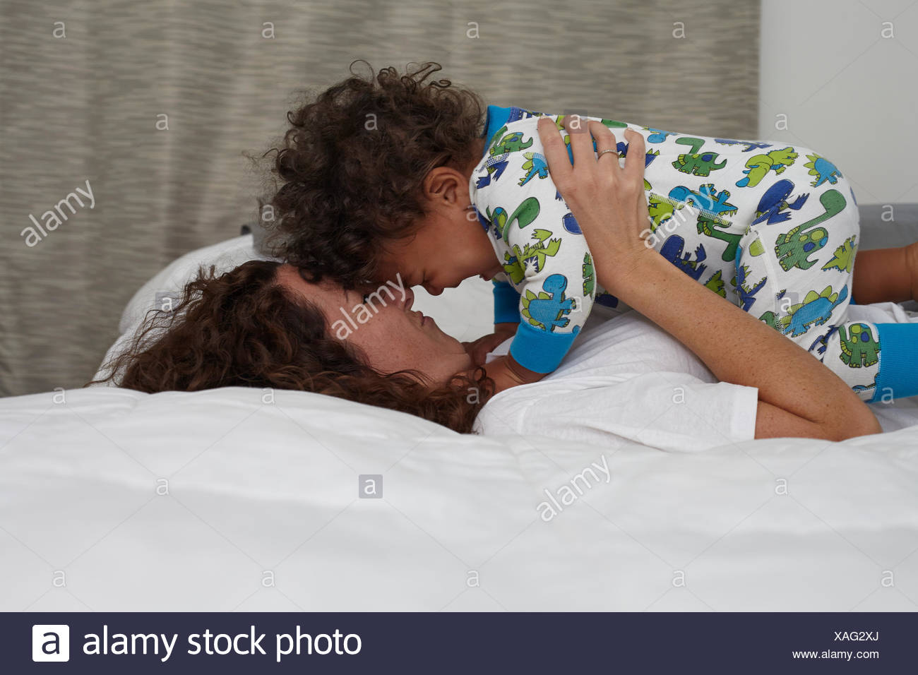 Young woman lying on bed face to face with toddler son - Stock Image