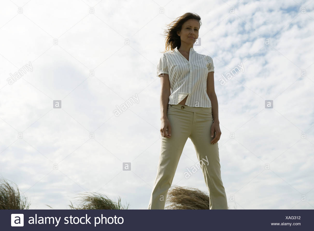 Woman outdoors standing with legs part, hair tousled by breeze - Stock Image