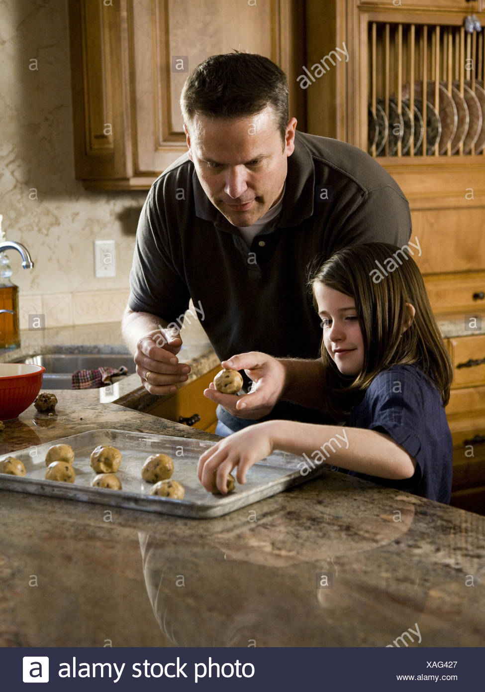 Girl in kitchen with man baking cookies - Stock Image