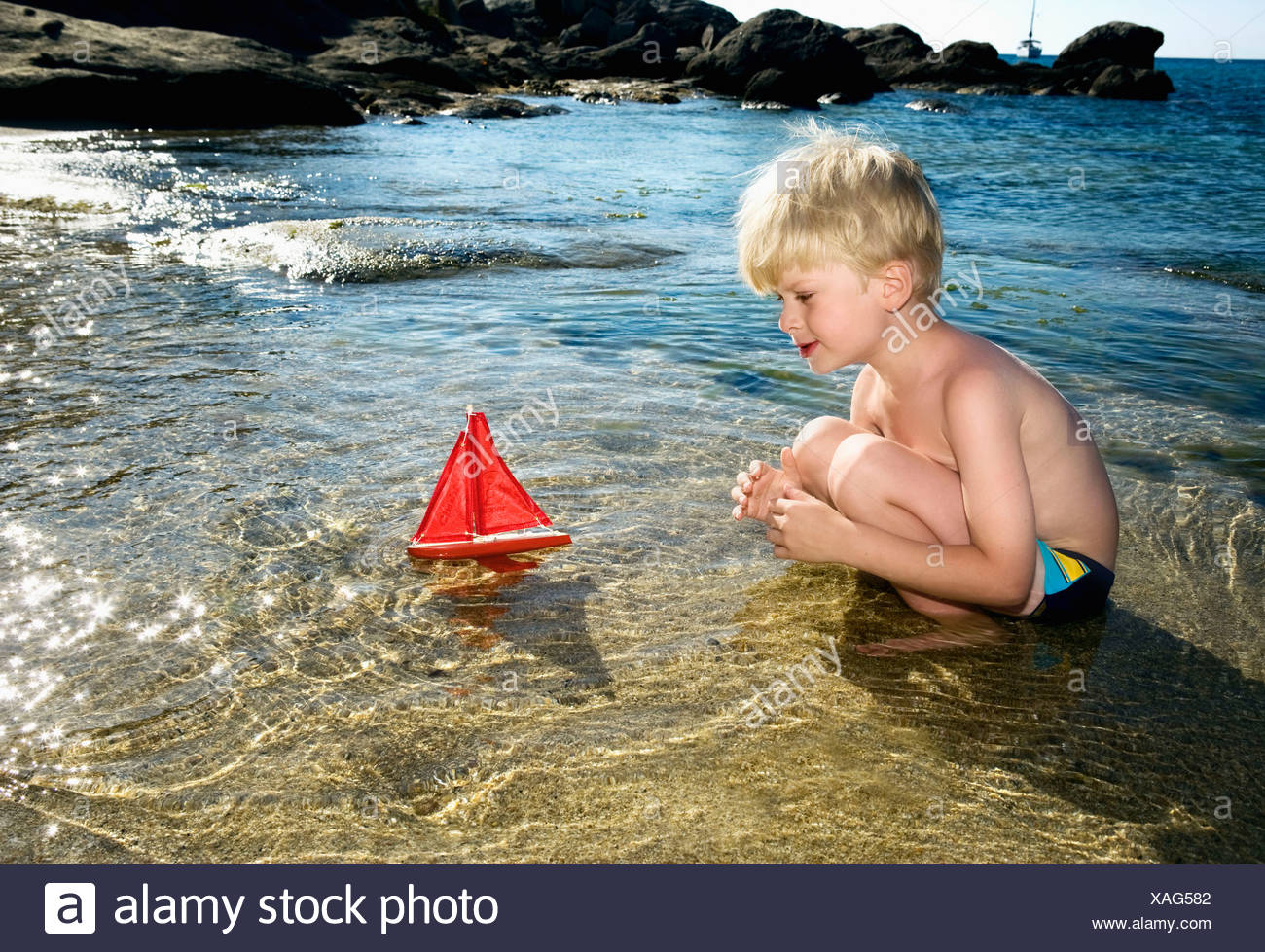 Young boy with a toy sailboat at the beach. Stock Photo