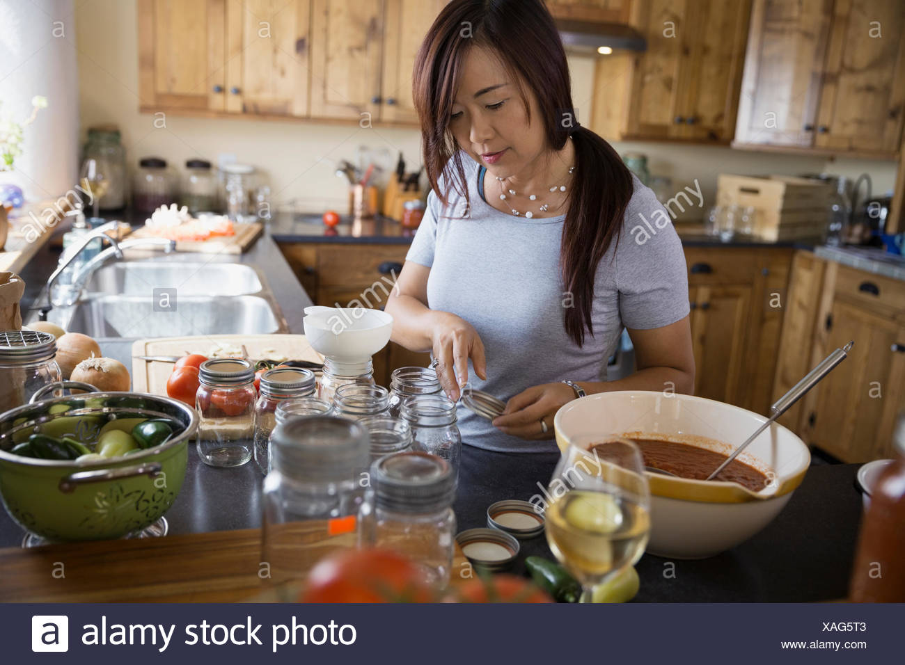 Woman canning tomato sauce in kitchen - Stock Image