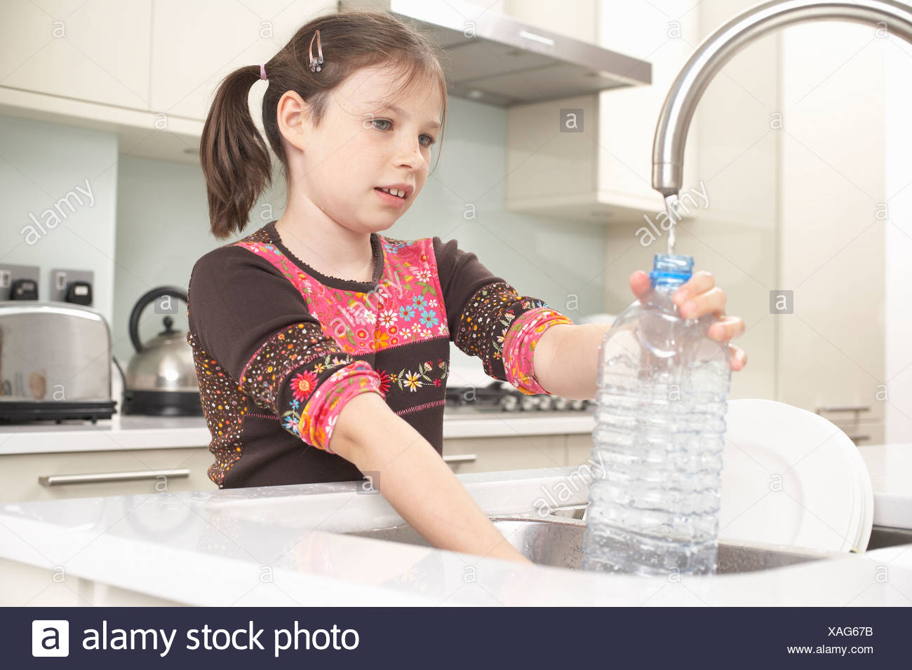 Girl filling up water bottle in kitchen - Stock Image