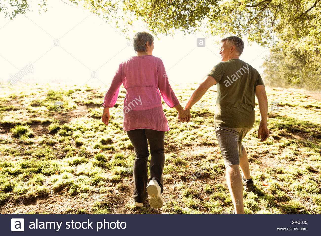 Rear view of mature couple power walking in park - Stock Image