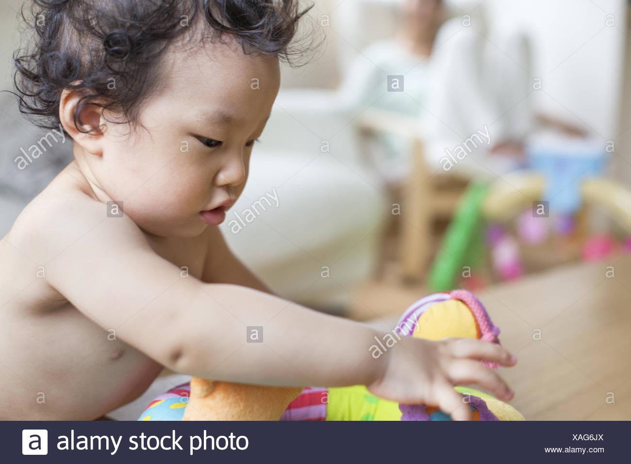 Baby boy playing indoors. - Stock Image
