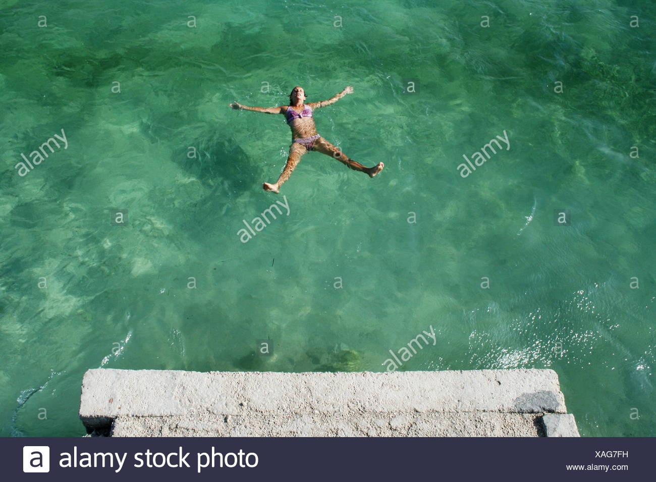Croatia, Dalmatia, Trogir, Mid-adult woman floating in green sea - Stock Image