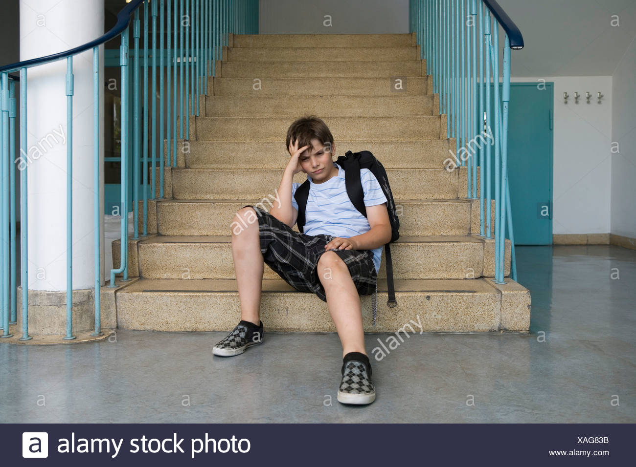 A worried pre-adolescent boy sitting on stairs in a school Stock Photo