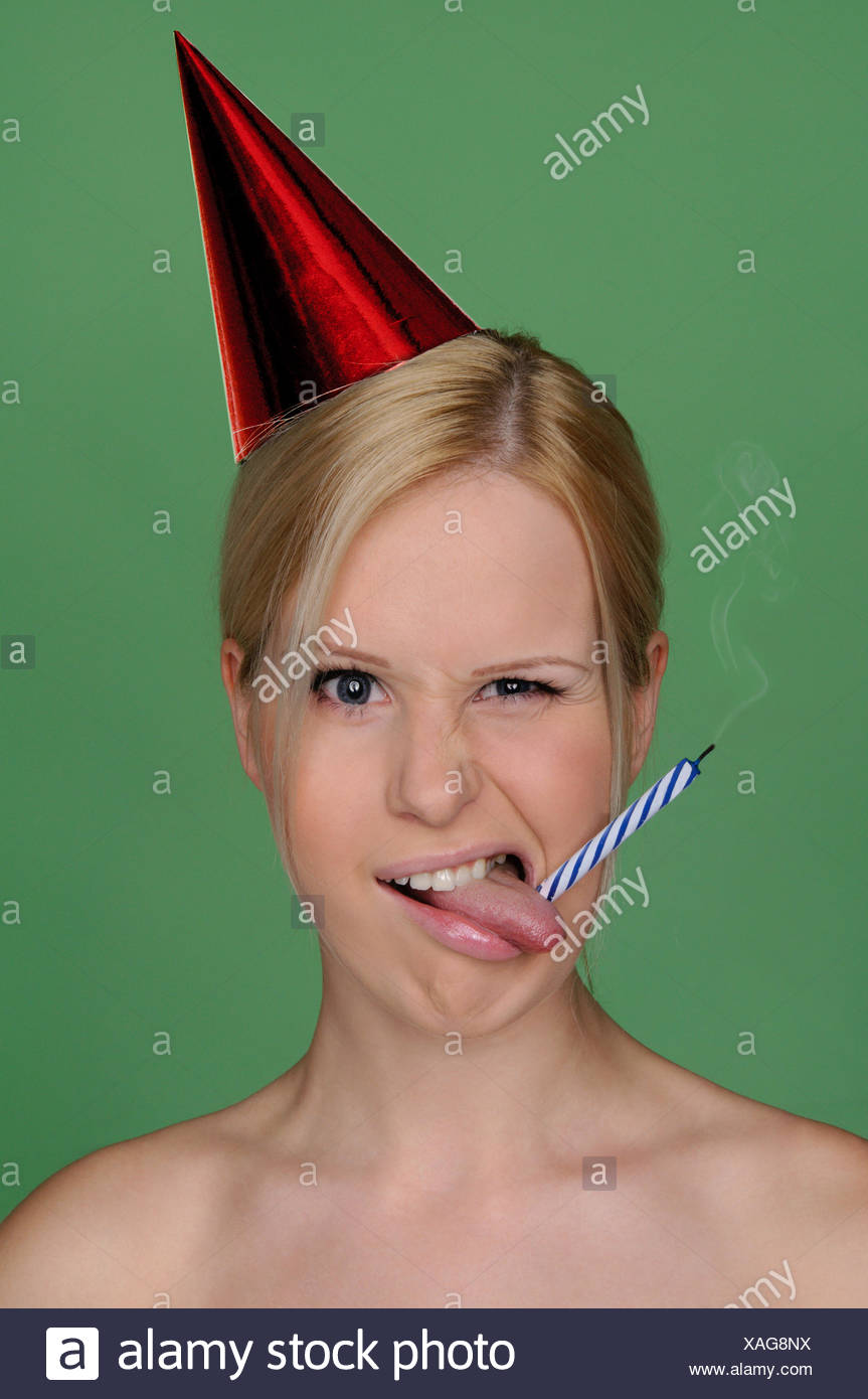 woman with candle extinguished and festive cap - Stock Image