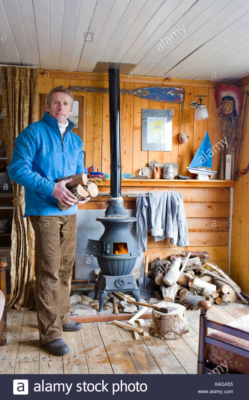 Man in living room putting log into wood burning stove Stock Photo