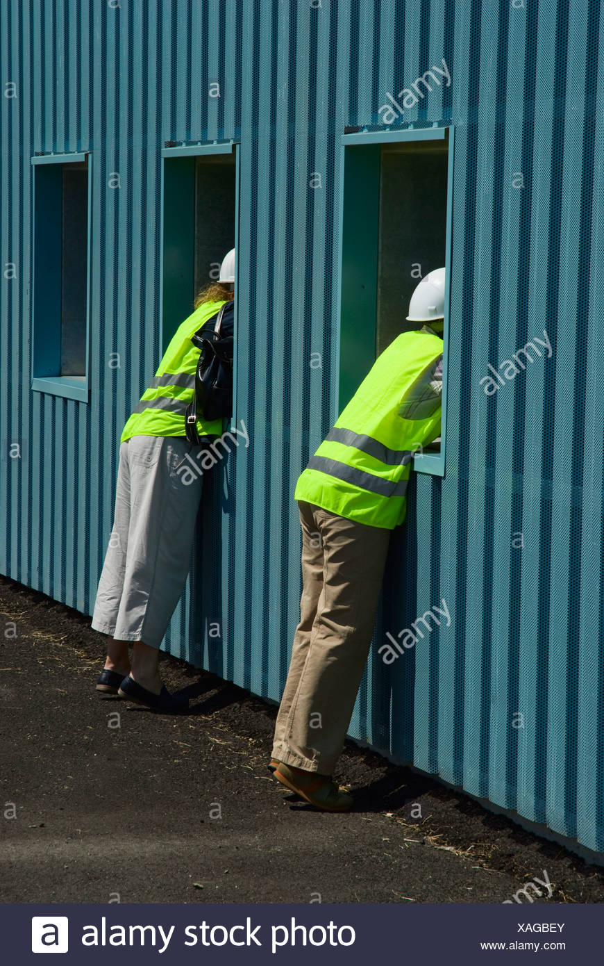 Visitors wearing hardhats and safety vests looking into the sanitation hall at the Sondermuelldeponie or hazardous waste deposi - Stock Image