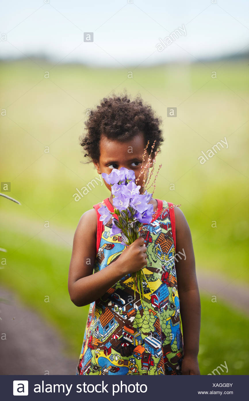 Sweden, Vastra Gotaland, Gullspang, Runnas, Girl (4-5) smelling bouquet - Stock Image