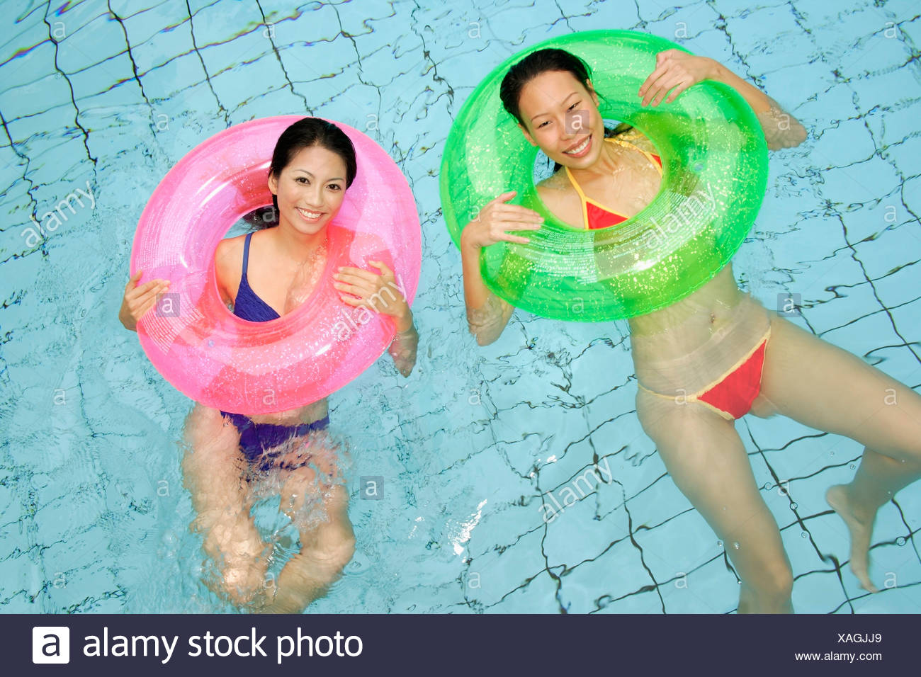Women in swimming pool, using inflatable rings, looking at camera Stock Photo