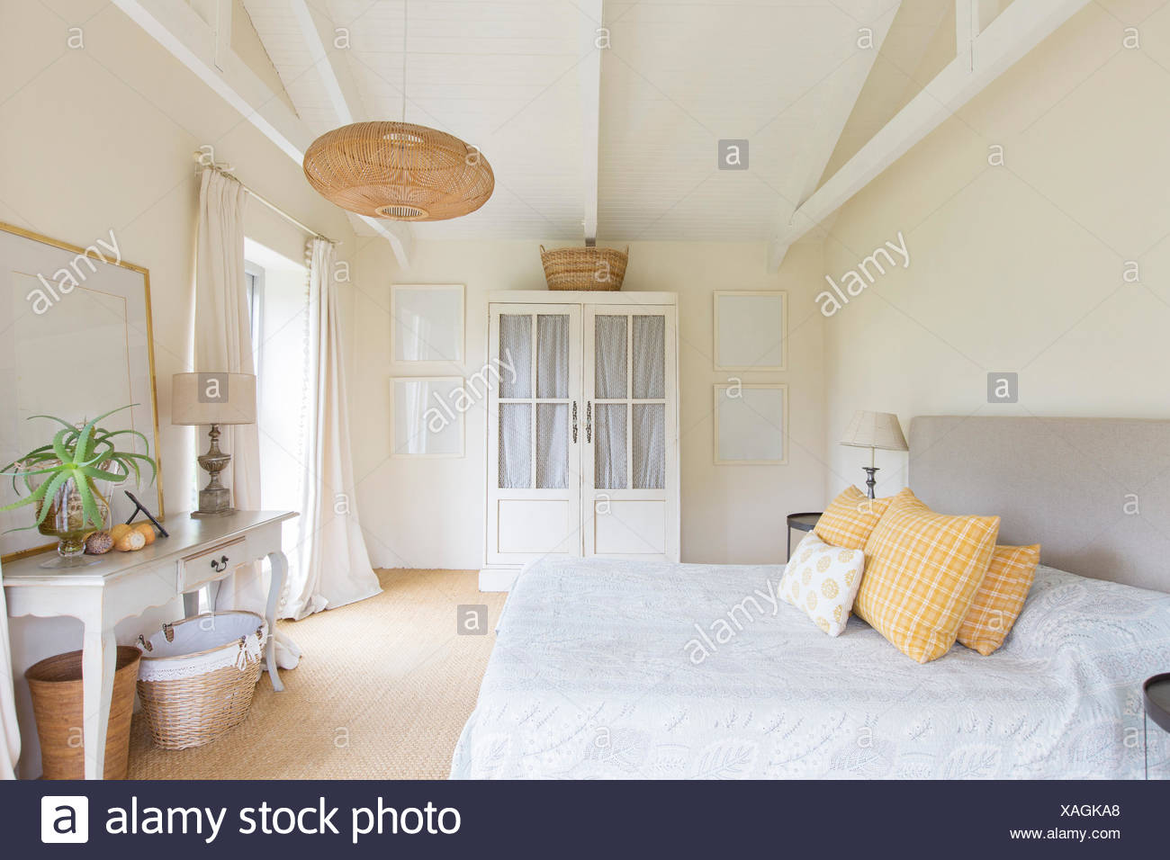 Bed and cabinet in bedroom of rustic house - Stock Image