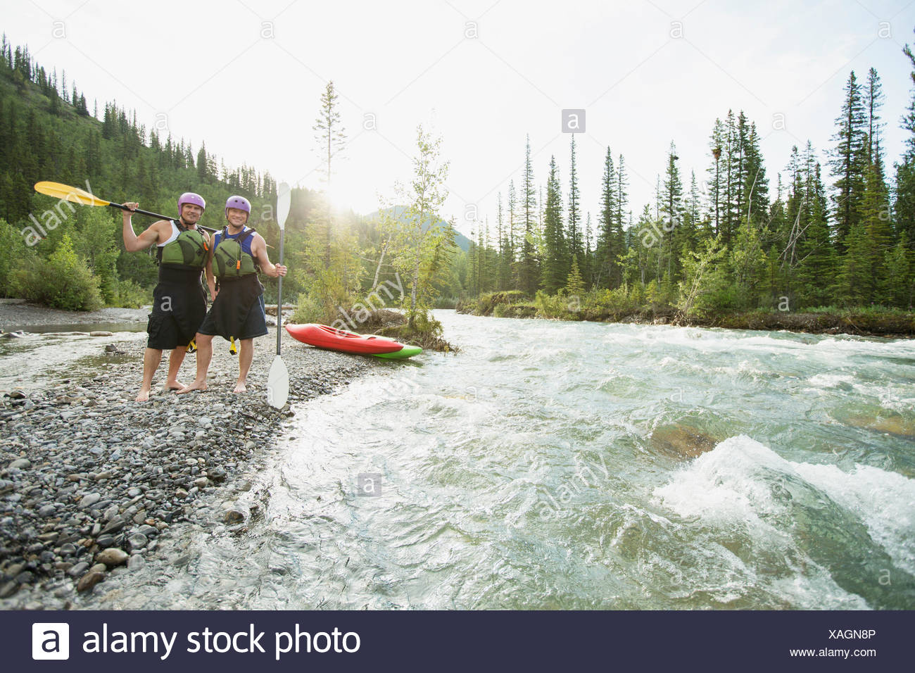 two male kayakers standing by a fast moving river - Stock Image