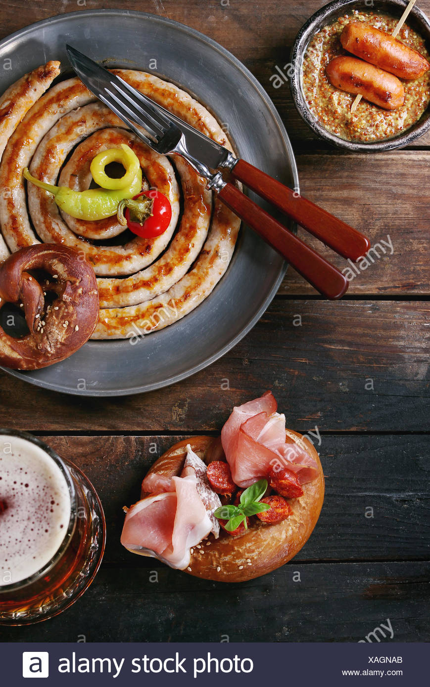 Big spiral fried sausage, meat snacks wienerwurst, ham, marinated chili peppers served in salted pretzels and plate with glass of lager beer and musta Stock Photo