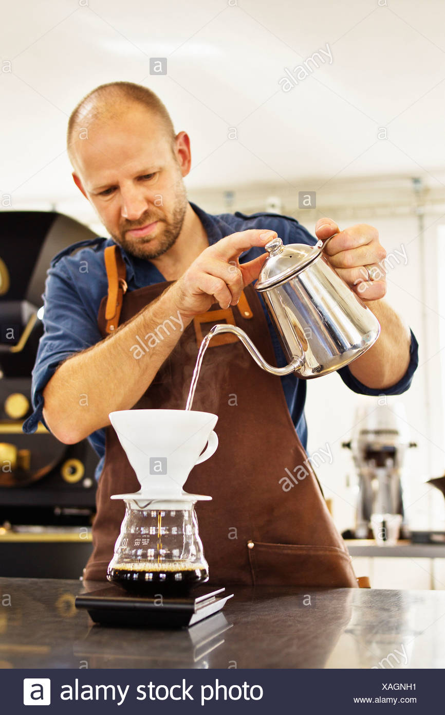 Barista pouring boiling water into coffee filter - Stock Image
