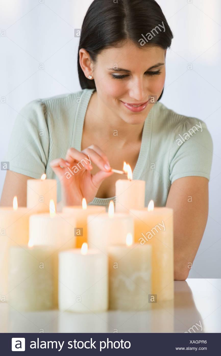 Woman lighting candles - Stock Image