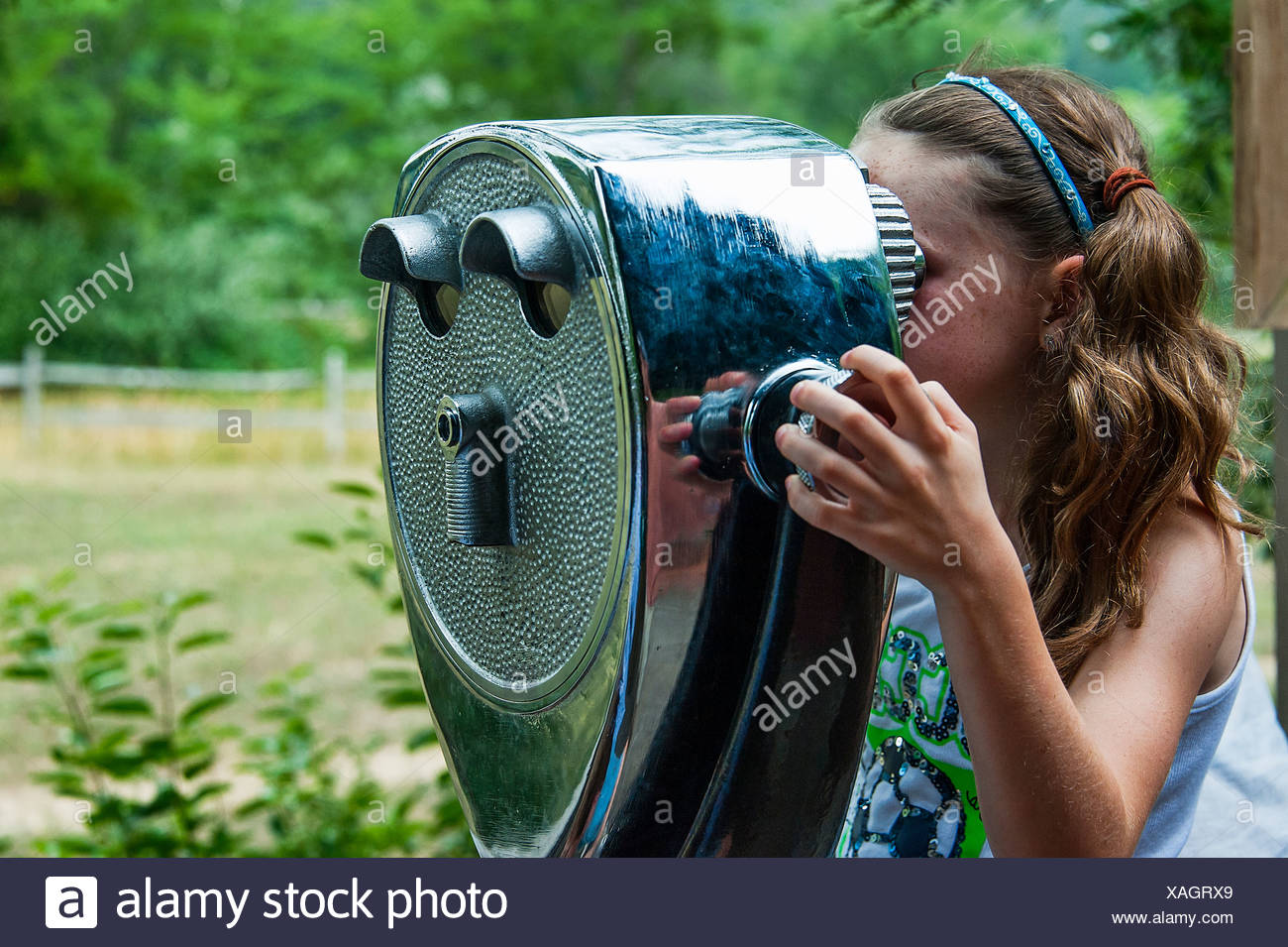 Girl looking through a viewing scope. - Stock Image