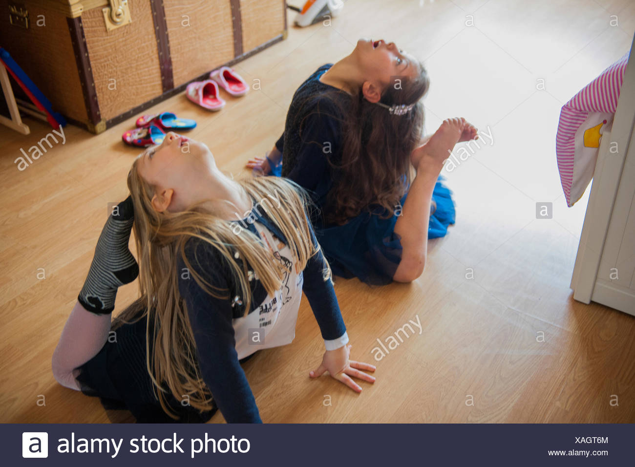 Girls stretching with toes touching heads - Stock Image
