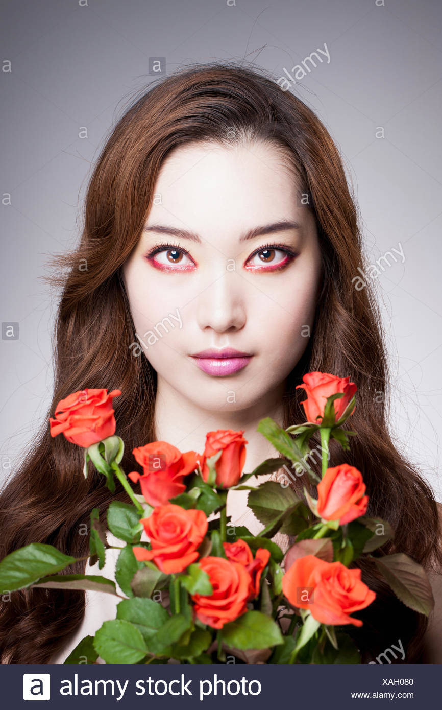 Portrait of young Korean woman in rwd eye liner with red roses - Stock Image
