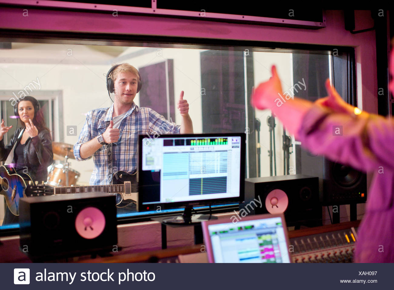 Young band recording in studio - Stock Image